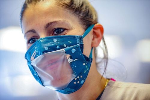 Woman wearing face mask with clear plastic window cut through it, so that you can see her mouth.